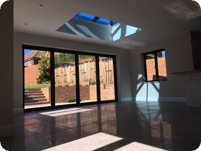 Inside or a modern extension with polished ceramic floor tiles, large patio doors and a skylight
